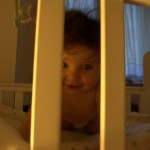 Little M peering through the gaps in her cot